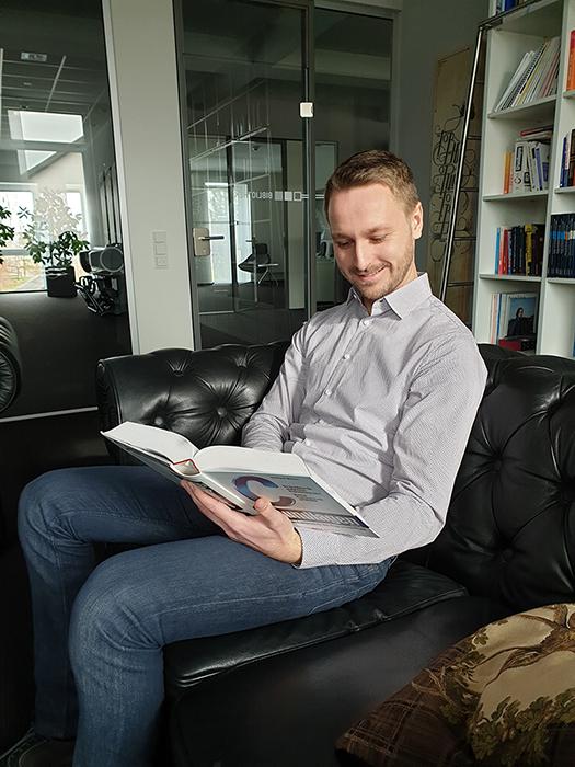 Vorstandsassistent Fabian Grünkemeier in der SYNAXON-Bibliothek. Bild: SYNAXON AG