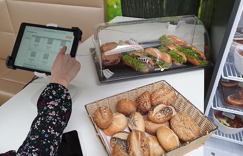 Tablet der selbstbedienBar, sowie Brötchen und belegte Brote. Bild: SYNAXON AG