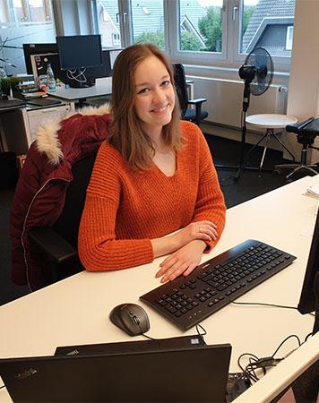 Junge Mutter Susanna an ihrem Schreibtisch in der SYNAXON AG. Bild: SYNAXON AG