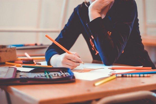 Mädchen am Schreibtisch, Hand stützt Kopf, arbeitet Schulmaterial ab. Bild: Pixabay